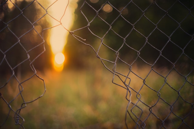 Sun glimpsed through gap in fence